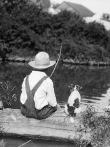 1920s 1930s Farm Boy Wearing Straw Hat And Overalls Sitting On Log With Spotted Dog Fishing