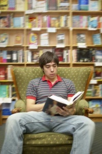 Reading- Boy reading in chair in small bookstore