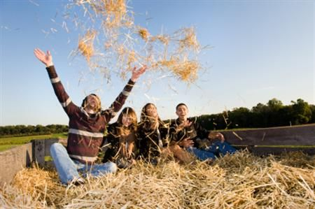 Thill and excitement fill smiling faces of young adults enjoying a seasonal hay ride. A scene of wholesome outdoor entertainment for a group of well dressed group of four people. Action filled shot as man on left throws hay into the air to the others surprise.